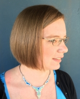 Portrait of Alisa Beer wearing glasses and a necklace